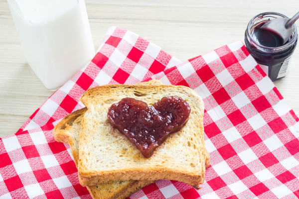 Breakfast toast with red heart jam symbol on a red checkered table cloth.